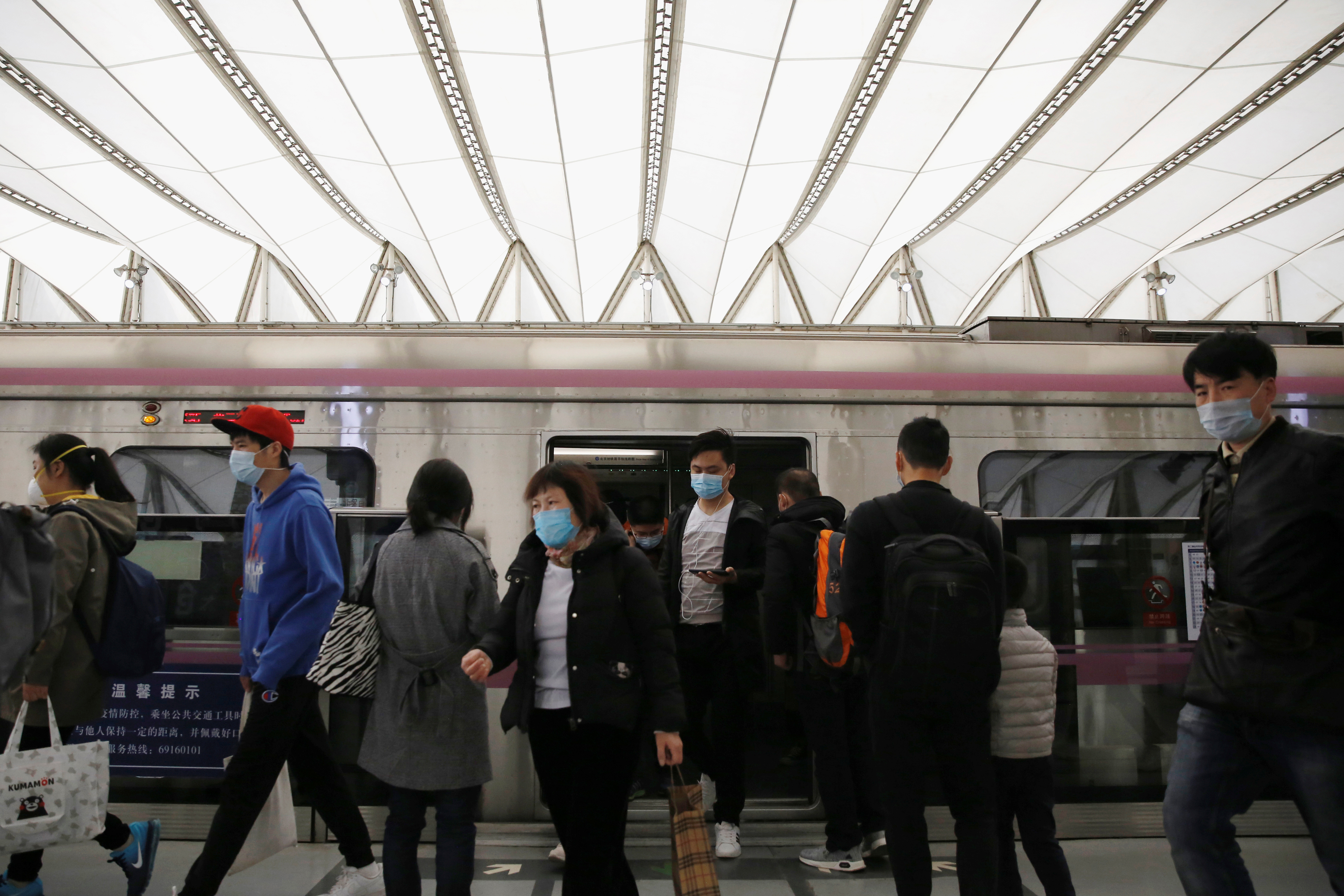 People wearing face masks get off a subway train at a subway station during morning rush hour in Beijing, as the spread of the novel coronavirus disease (COVID-19) continues in the country, in China, on April 7, 2020. Photo: Reuters