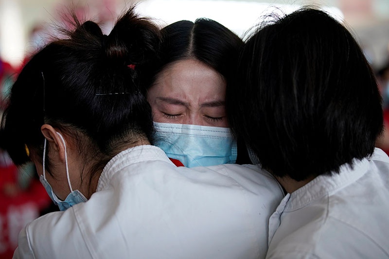 Medical workers hug at the Wuhan Tianhe International Airport after travel restrictions to leave Wuhan, the capital of Hubei province and China's epicentre of the novel coronavirus disease (COVID-19) outbreak, were lifted, on April 8, 2020. Photo: Reuters