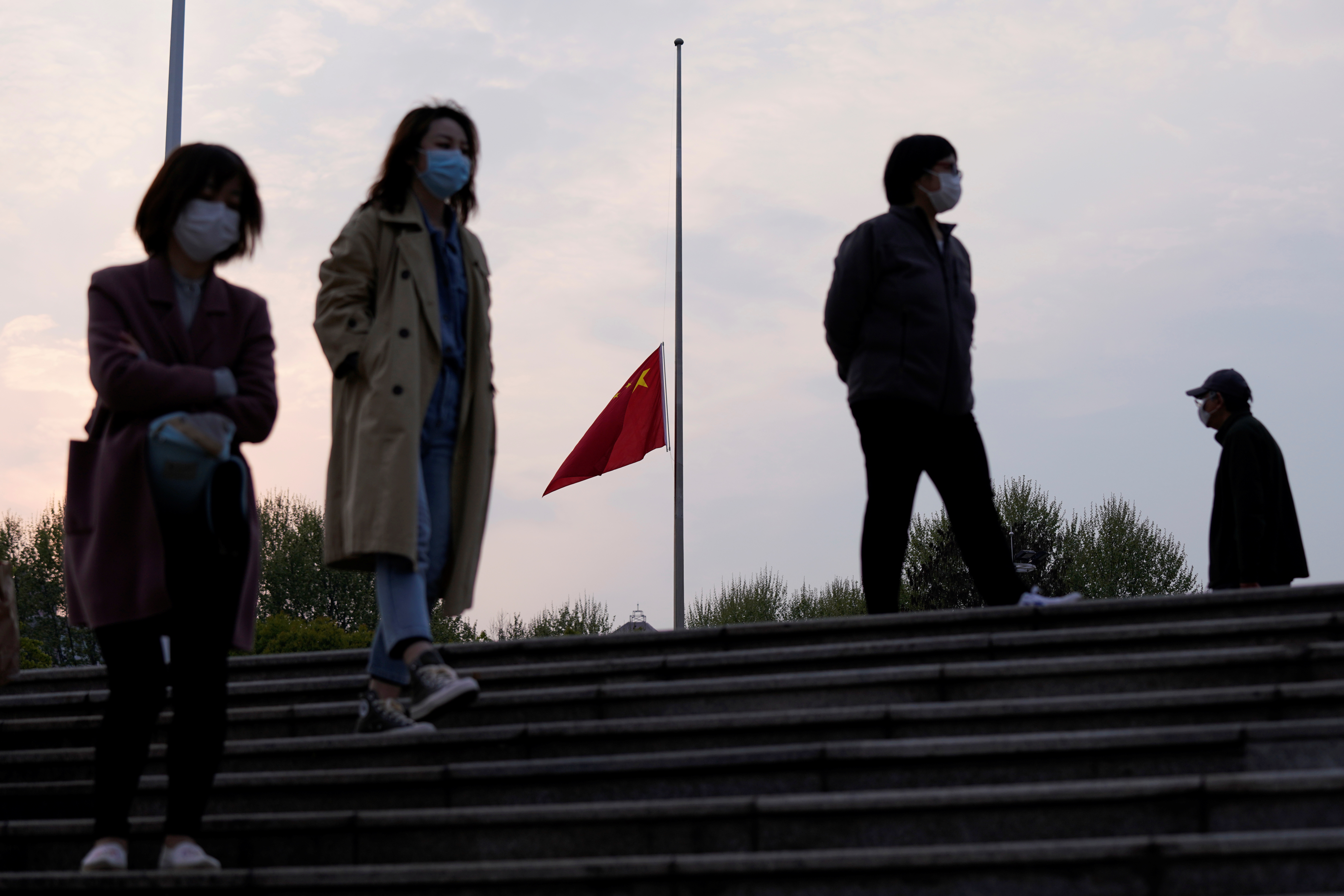 People wearing face masks walk past the Chinese national flag flying at half mast in Wuhan, Hubei province, as China holds a national mourning for those who died of the coronavirus disease (COVID-19), on the Qingming tomb-sweeping festival, April 4, 2020. Photo: Reuters