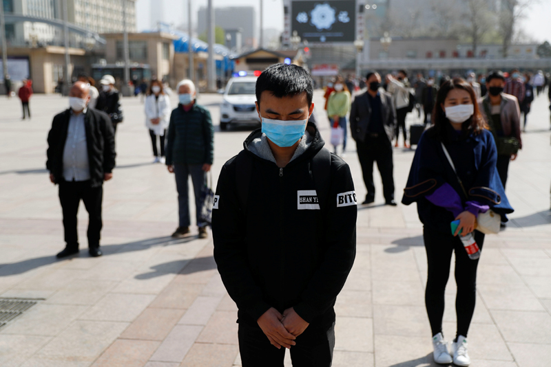 People wearing face masks stand to pay tribute as China holds national mourning for those who died of the coronavirus disease (COVID-19), on the Qingming tomb-sweeping festival, in Beijing April 4, 2020. Photo: Reuters