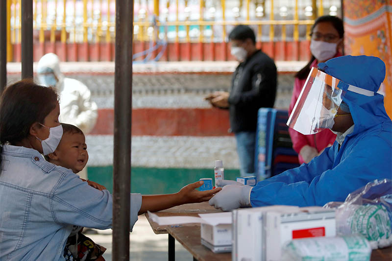 A health worker in a protective gear takes a blood sample from a woman at the makeshift rapid testing center for the coronavirus disease (COVID19), in Lalitpur, on Tuesday, April 14, 2020. Photo: Reuters