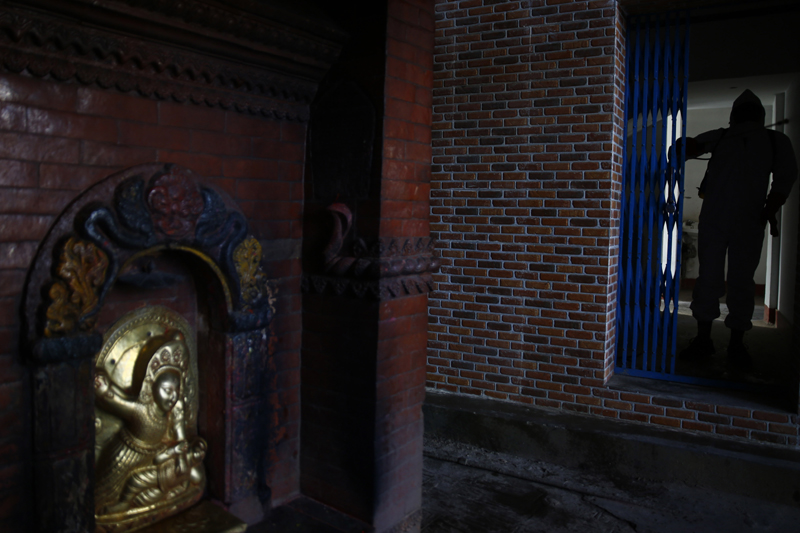 A youth in a protective suit disinfects a temple premises in Kathmandu, on the tenth day of government-imposed lockdown, on Thursday, April 02, 2020. Photo: Skanda Gautam/THT