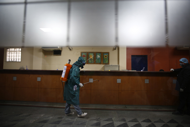 A man in protective suit is seen disinfecting the Himalayan Bank premises in Kathmandu on Sunday, April 12, 2020, the 20th day of nationwide Coronavirus-lockdown which came into effect from March 24. Photo: Skanda Gautam/THT