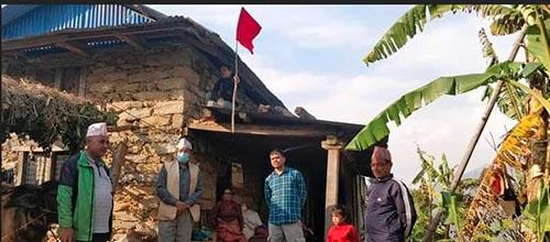 A local level representative placing a red flag on the rooftop of a foreign returneeu2019s house in Dolakha, on Wednesday. Photo: THT