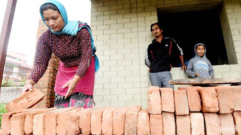 Earthquake victim Anjana Tajale is  seen picking up bricks for the construction of her  two-room house in Bhaktapur. Photo: AFP