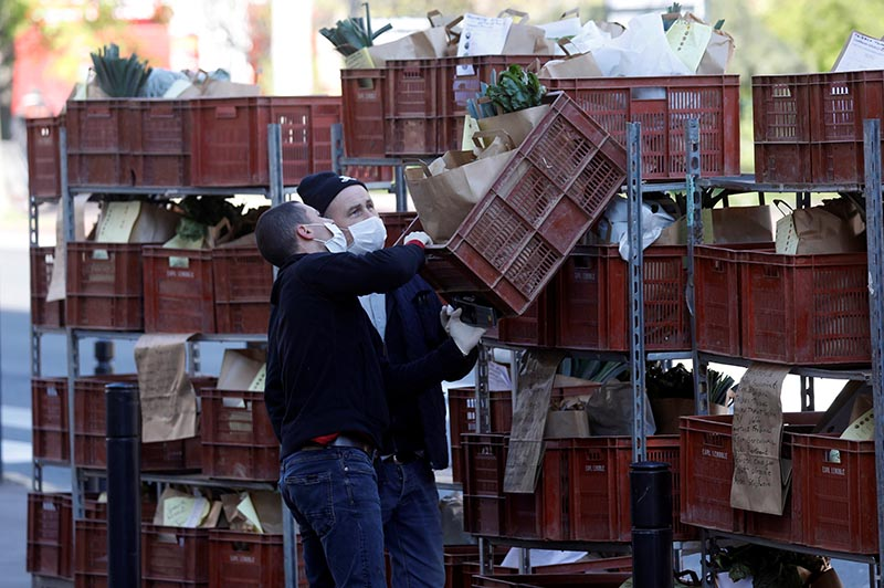 Vegetable grower Dominique Lenoble and his son set up a pick-up point for people who placed orders to retrieve vegetables during the outbreak of Coronavirus disease (COVID-19) in Joinville-le-Pont, France, on April 1, 2020. Photo: Reuters