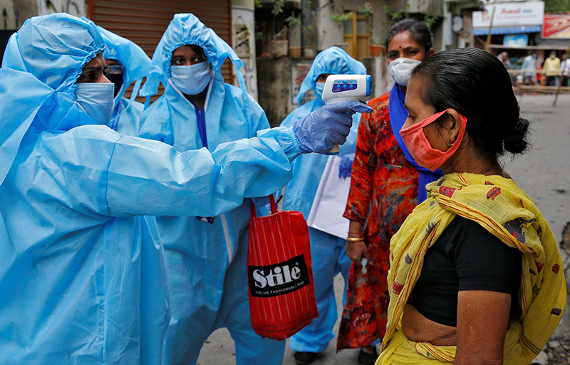 A health worker wearing protective gear uses an infrared thermometer to check the temperature of a woman during a door-to-door verification of people to find out if they have developed any coronavirus disease (COVID-19) symptoms, in a residential area in Kolkata, India, April 21, 2020. Photo: Rueters