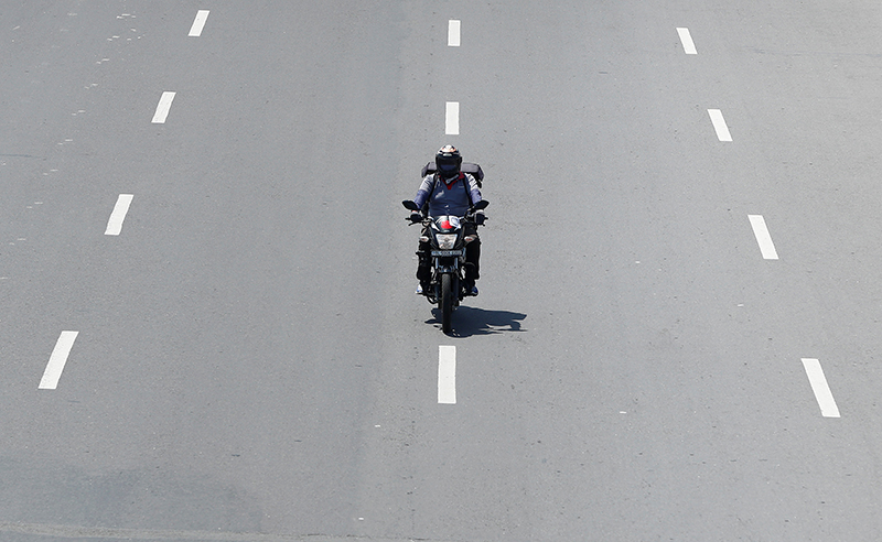 Delivery worker Devender Singh, who works for Licious, an online meat store, rides his bike on a deserted road, during a 21-day nationwide lockdown to slow the spreading of the coronavirus disease (COVID-19), in New Delhi, India, on April 6, 2020. Photo: Reuters