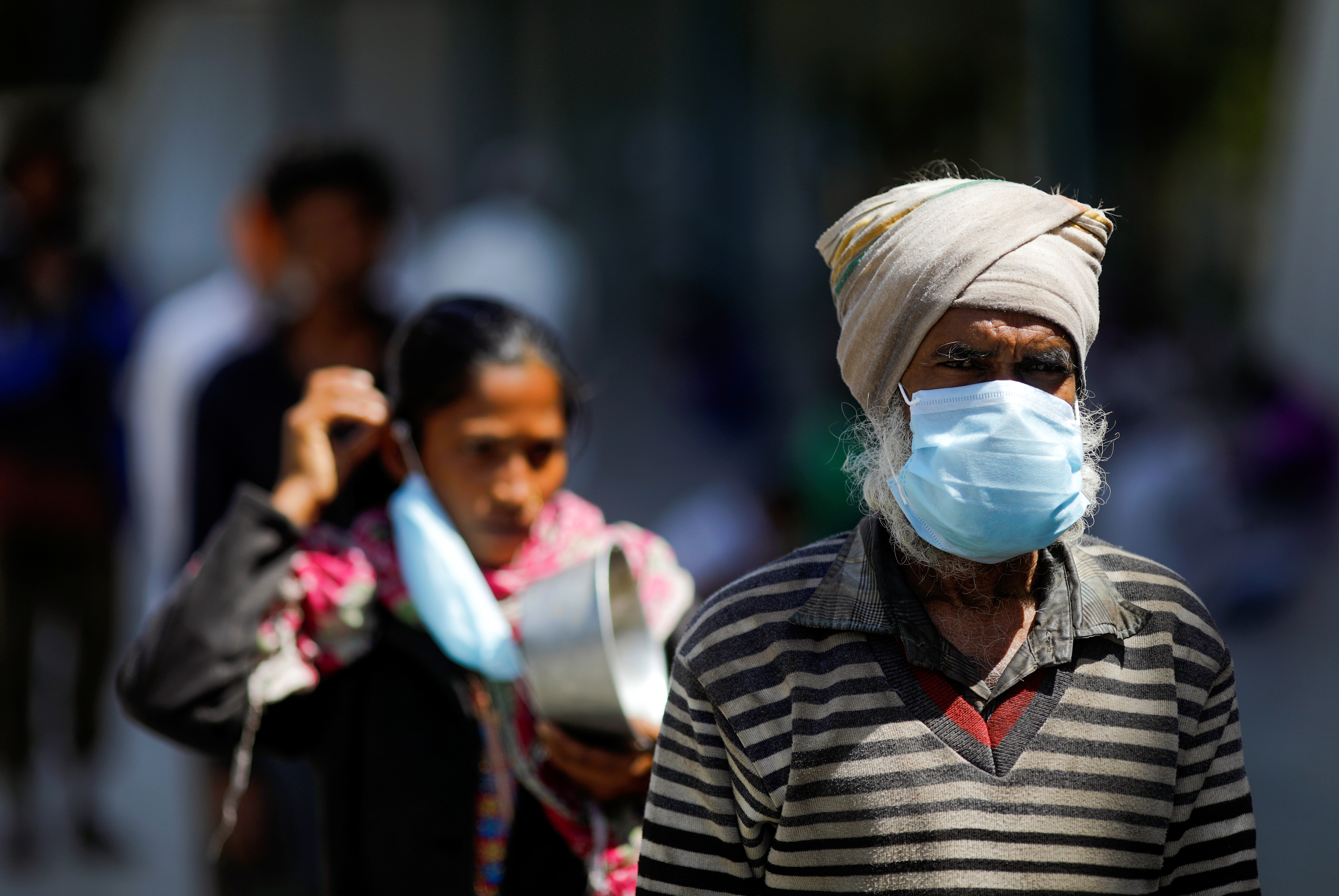 People wearing protective masks queue for food inside a sports complex turned into a shelter, during a 21-day nationwide lockdown to slow the spread of the coronavirus disease (COVID-19), in New Delhi, India, April 4, 2020. REUTERS/Adnan Abidi