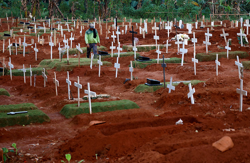 FILE - A municipality worker walks among graves at a cemetery complex provided by the government for coronavirus disease (COVID-19) victims in Jakarta, Indonesia, on April, 22, 2020. Photo: Reuters