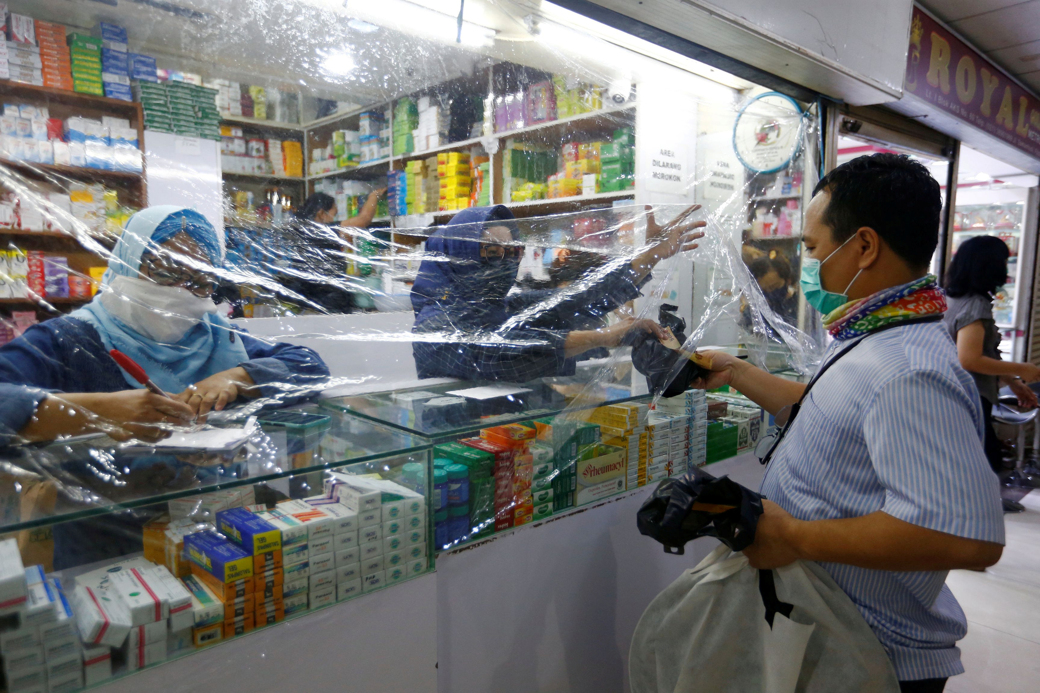A customer wearing protective face mask makes his transaction through a plastic barrier as a preventive measure against the coronavirus disease (COVID-19) in Jakarta, Indonesia, April 2, 2020. REUTERS/Ajeng Dinar Ulfiana