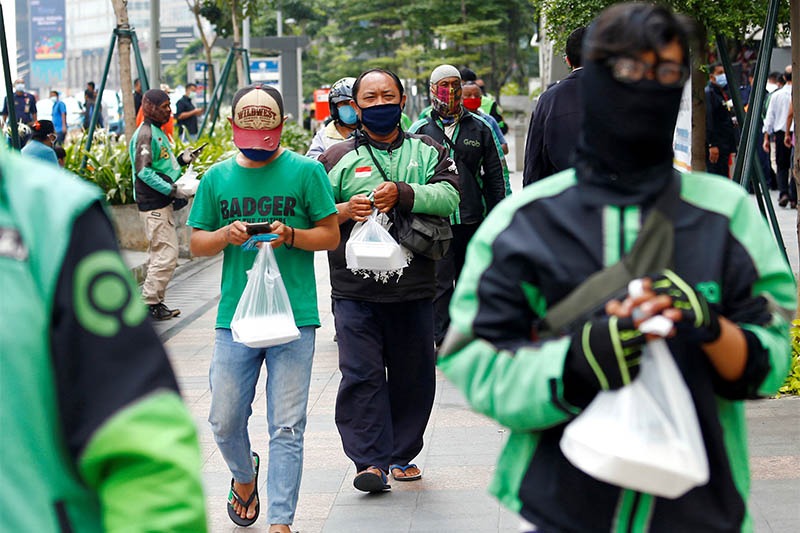 Online motorbike taxi drivers hold boxes of meals as people queue for free food given by a company amid spread of the coronavirus disease (COVID-19) in Jakarta, Indonesia April 17, 2020. Photo: Reuters