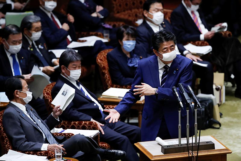 Japan's Prime Minister Shinzo Abe, wearing a protective face mask, gestures next to Japan's Finance Minister Taro Aso during an upper house parliamentary session, following an outbreak of the coronavirus disease (COVID-19), in Tokyo, Japan April 1, 2020. Photo: Reuters