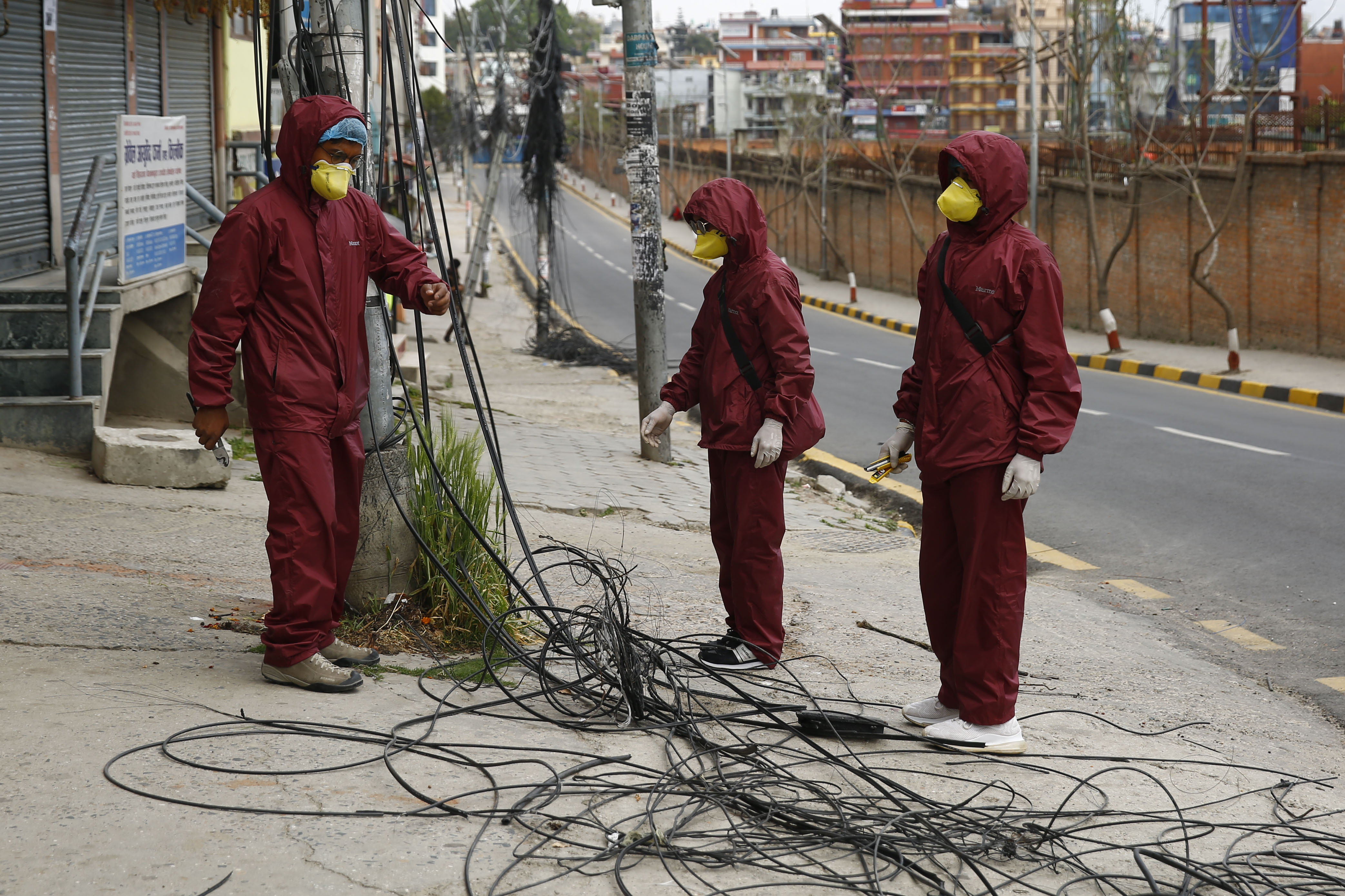 Broadband technicians wearing protective gear while fixing internet lines along a street on the ninth day of government-imposed lockdown, in Kathmandu, on Wednesday, April 01, 2020. Photo: Skanda Gautam/THT