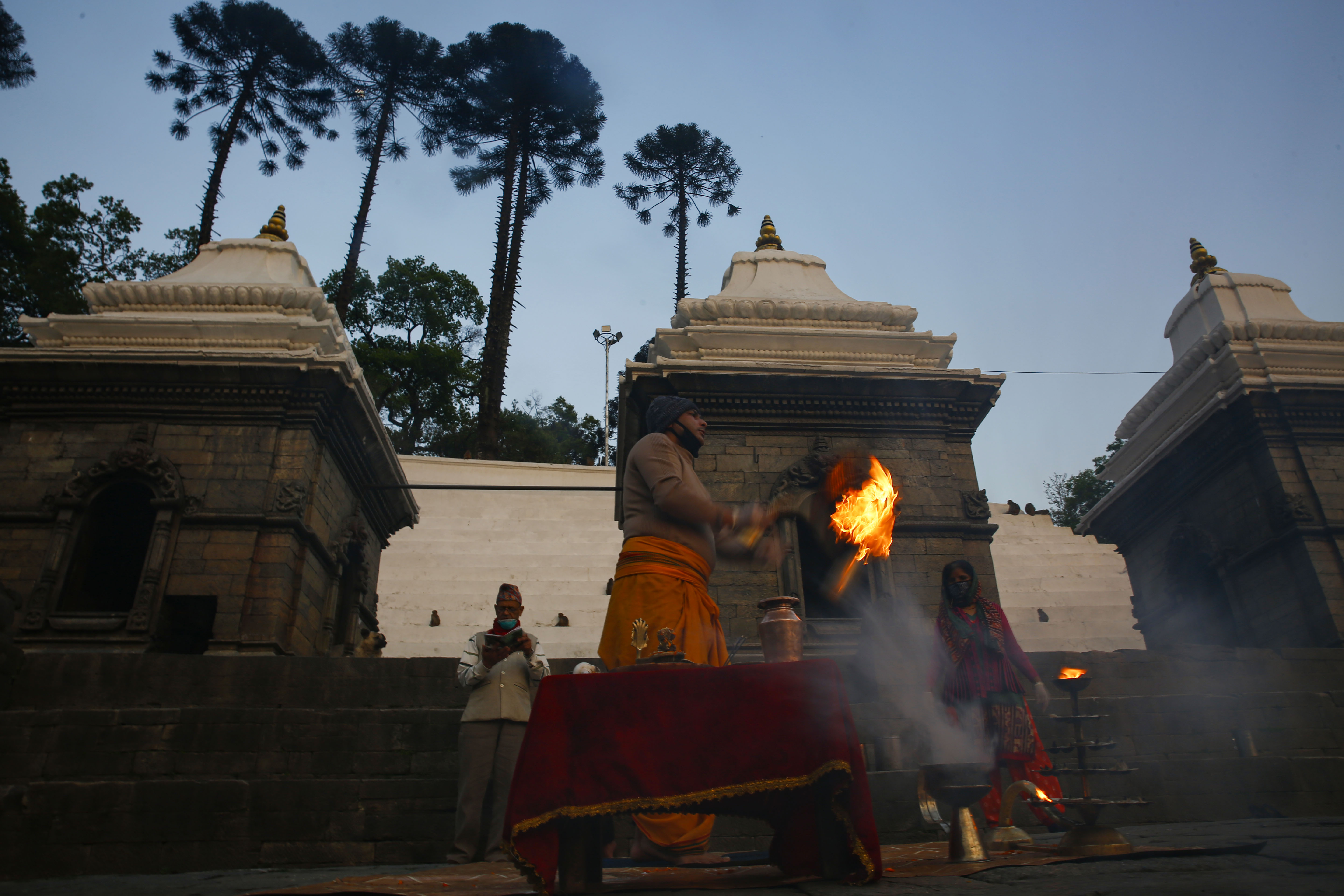 A priest performs the religious evening Aarati ritual inside the deserted Pashupatinath Temple on the twelveth day of the government imposed nationwide lockdown, in Kathmandu, on Saturday, April 4, 2020. Photo: Skanda Gautam/THT