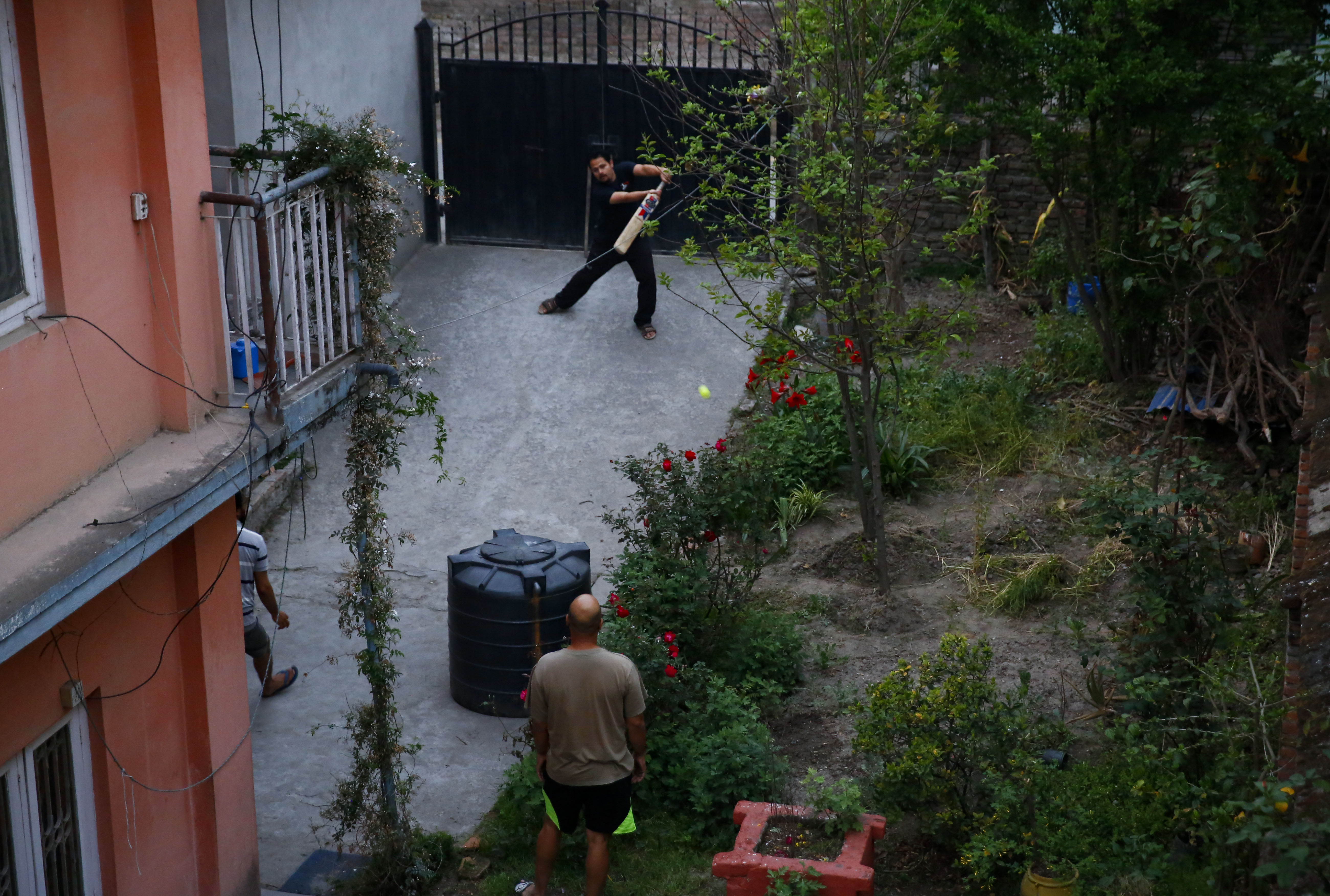 People seen playing cricket inside a house compound on the fourteenth day of government imposed nationwide emergency lockdown, in Kathmandu, on Monday, April 6, 2020.  Photo: Skanda Gautam/THT
