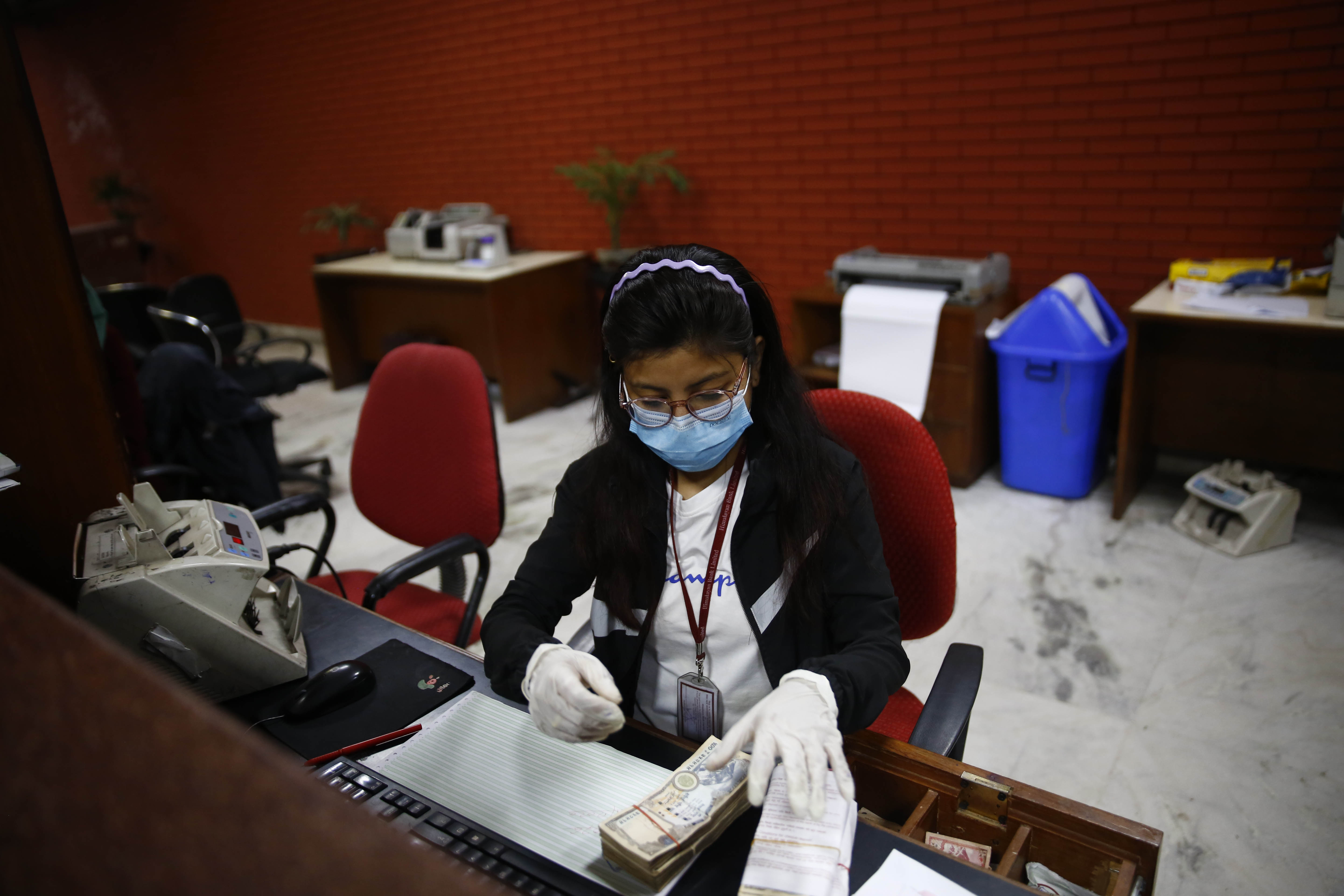 A teller wearing facemask and gloves counts cash at a bank, amid concerns over the spread of coronavirus contagion, on the eighteenth day of the government imposed lockdown, in Kathmandu, on Friday, April 10, 2020. Photo: Skanda Gautam/THT