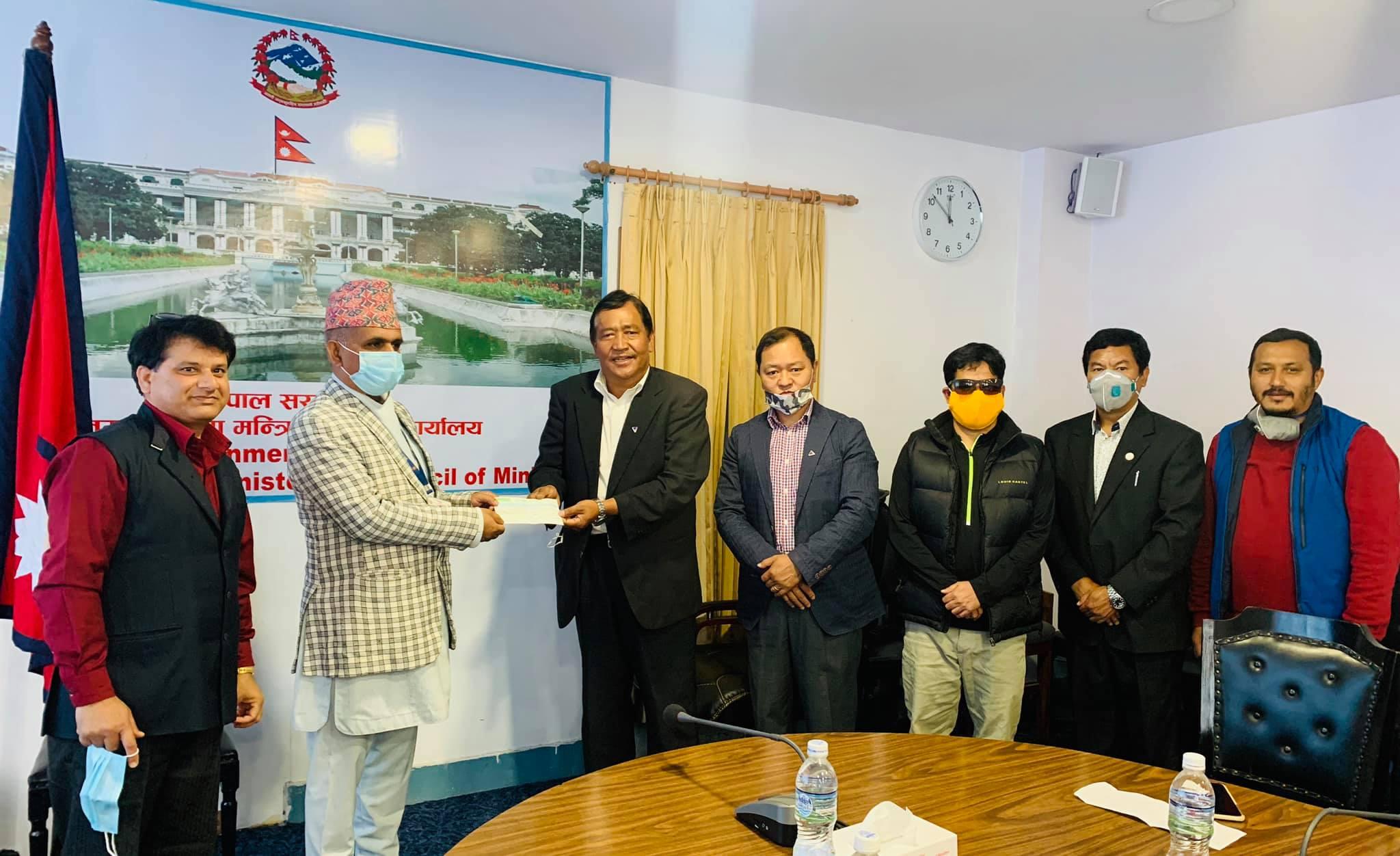NMA President Santa Bir Lama is handing over cheque to the Mahendra Prasad Guragai. Photo: Nepal Mountaineering Association