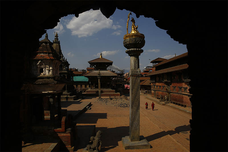 Two women walk along the deserted Patan Durbar Square, a UNESCO World Heritage Site, on the eleventh day of nationwide lockdown, amid concerns over the spread of coronavirus, in Lalitpur, on Friday, April 03, 2020. Photo: Skanda Gautam/THT