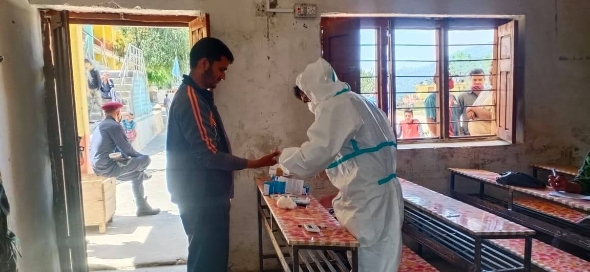 A health worker in personal protective equipment carrying out rapid diagnostic tests on individuals quarantined at Badimalika Secondary School, in Badimalika Municipality of Bajura district, on Friday, April 10, 2020. Photo: Prakash Singh/THT