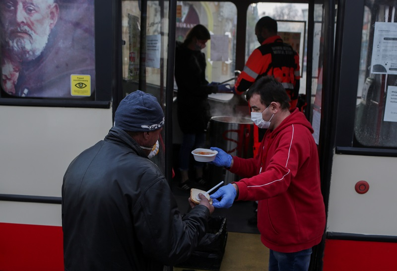 A volunteer wearing protective gloves and a face mask gives out bread and soup outside a charity bus, that drives around cities delivering free meals to homeless and people in need, as the coronavirus disease (COVID-19) outbreak continues in Sopot, Poland, April 13, 2020. REUTERS/Matej Leskovsek REFILE - CORRECTING DATE