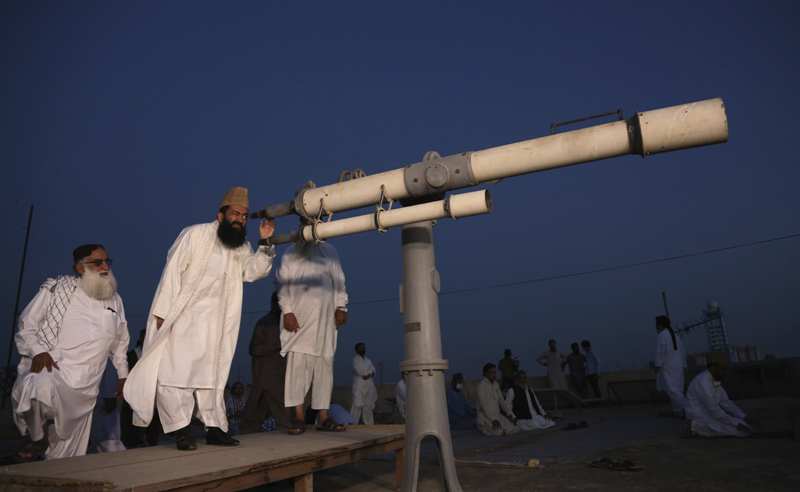 Clerics of Pakistan's Moon Sighting Committee search the sky with a telescope for the new moon that signals the start of the Muslim fasting month of Ramadan, in Karachi, Thursday, April 23, 2020. Photo: AP