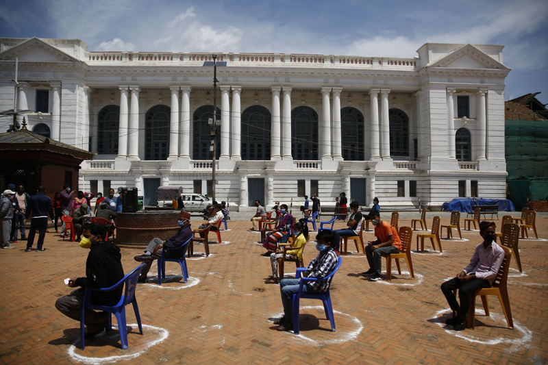 People sit on chairs placed on markings for a rapid test, at Basantapur Durbar Square, in Kathmandu, on the 26th day of lockdown, on Saturday, April 18, 2020. Photo: Skanda Gautam/THT