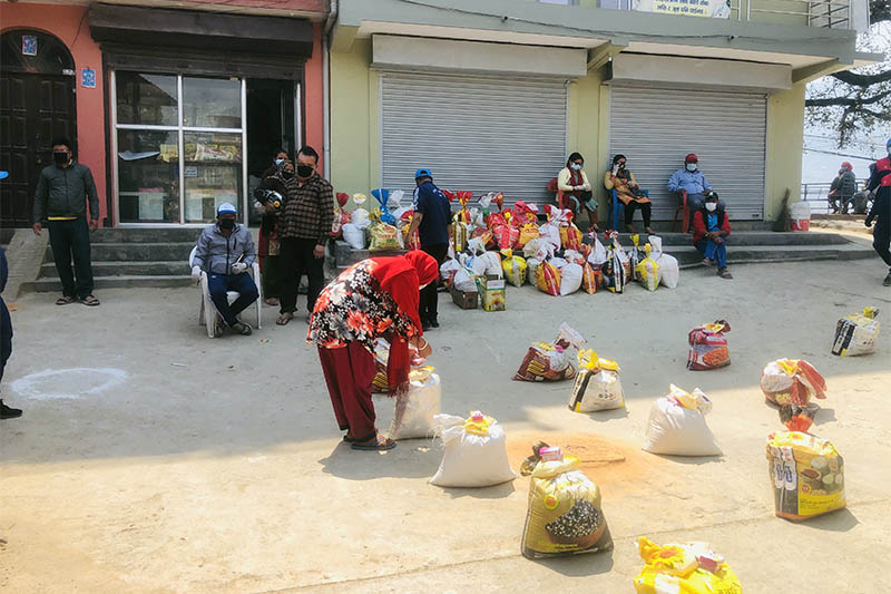 FILE - A woman collects relief items distributed by Chandragiri Municipality in Naikap, on Tuesday, April 07, 2020. Photo: THT