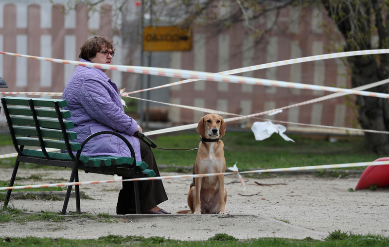 A view shows a woman and a dog on a taped-off playground amid the outbreak of the coronavirus disease (COVID-19) in Moscow, Russia April 27, 2020. Photo: Reuters