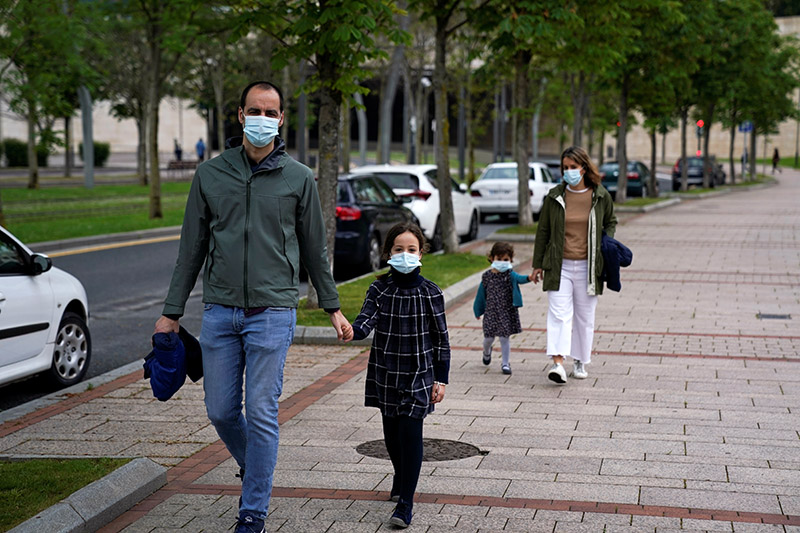 A family wearing protective masks takes a walk after restrictions were partially lifted for children for the first time in six weeks, during the coronavirus disease (COVID-19) outbreak in Bilbao, Spain, on April 26, 2020. Photo: Reuters