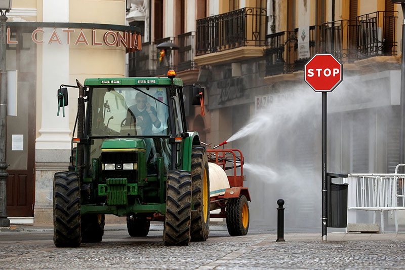 A farmer in a tractor disinfects a street, amid the coronavirus disease (COVID-19) outbreak, in downtown Ronda, southern Spain, on April 7, 2020. Photo: Reuters