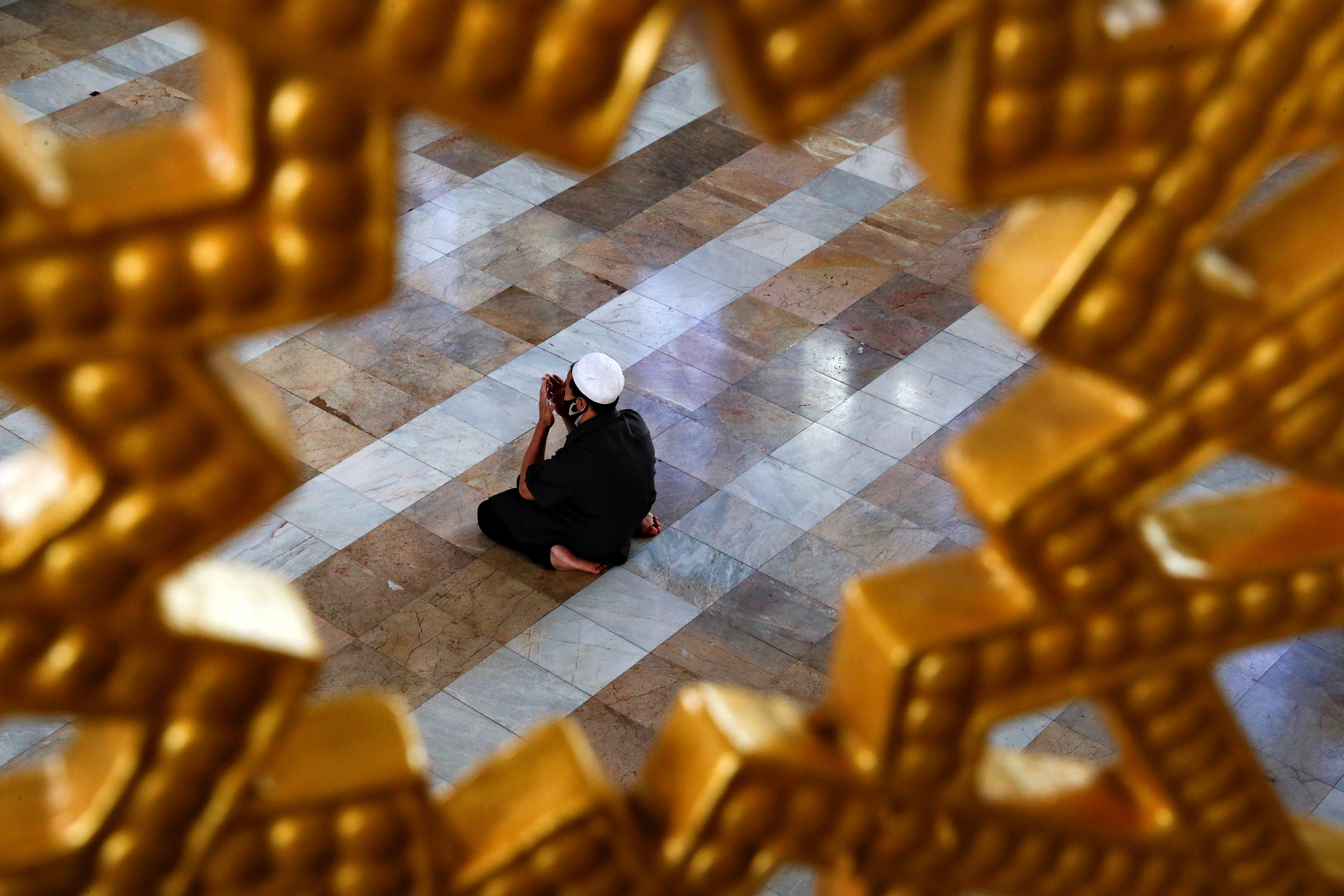 A Muslim man wearing a protective face mask prays at a mosque on the first day of the holy fasting month of Ramadan, amid the coronavirus disease (COVID-19) outbreak, in Bangkok, Thailand, on Friday, April 24, 2020. Photo: Reuters