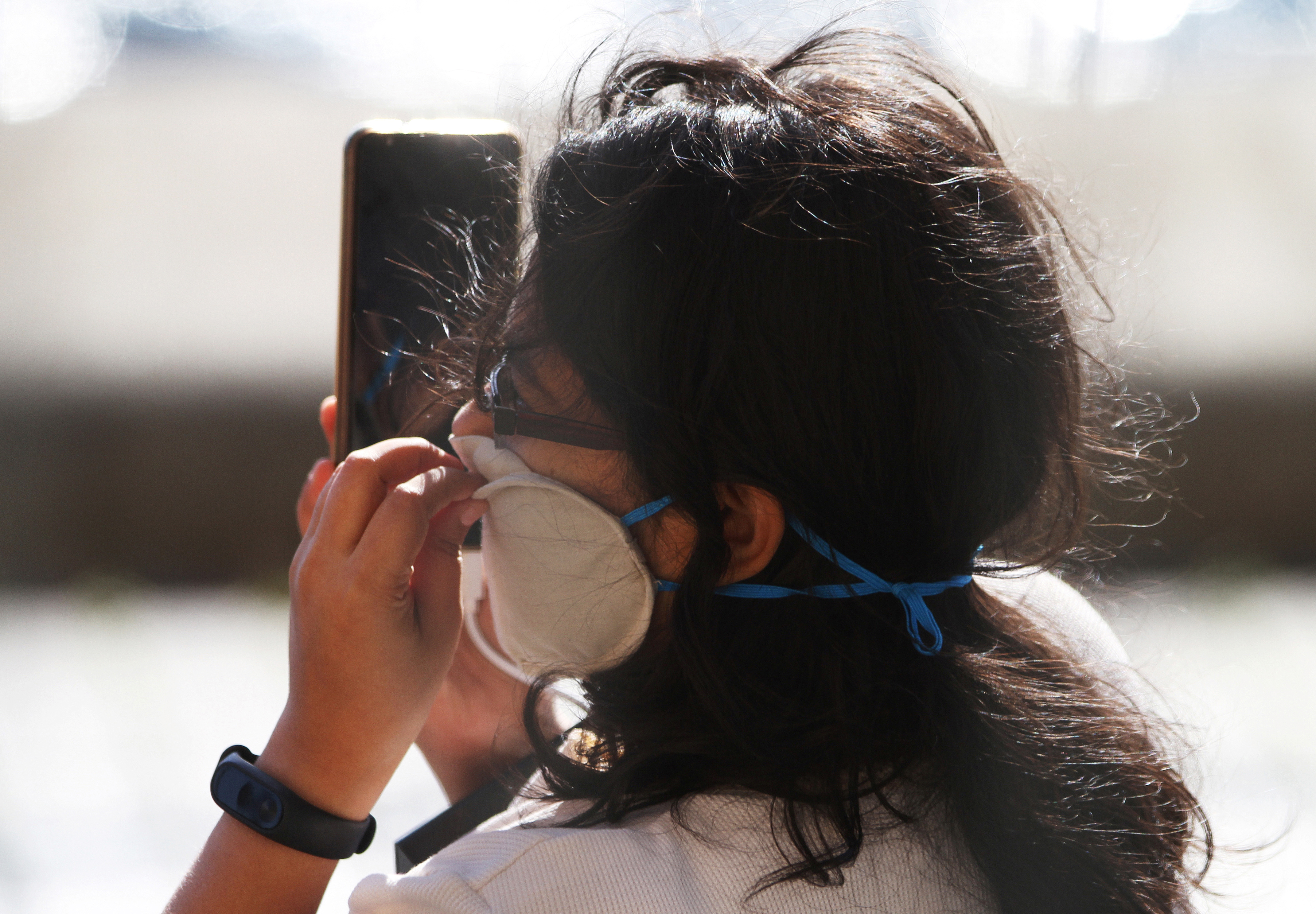 A woman holds a mobile phone as she touches her protective face mask while the spread of the coronavirus disease (COVID-19) continues, London, Britain, April 19, 2020. Photo: Reuters