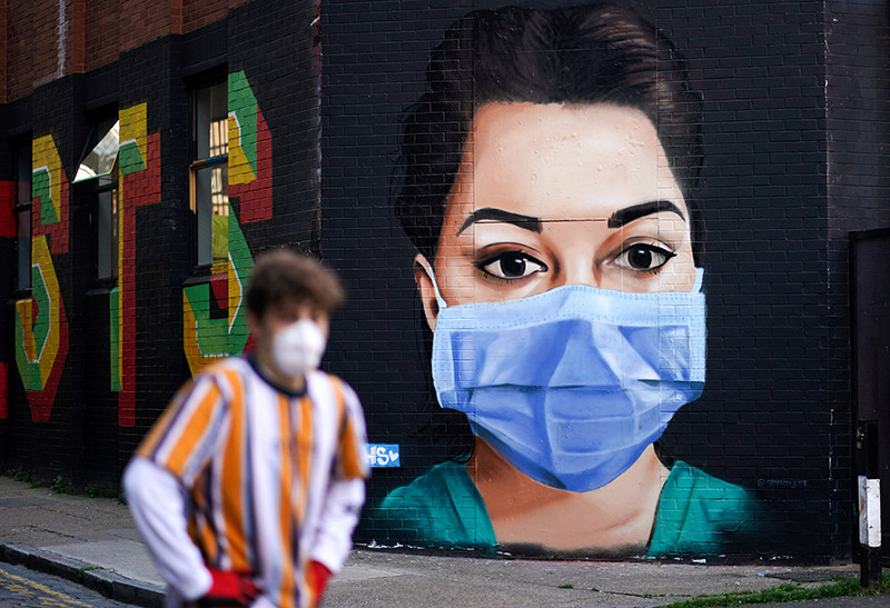 A man wearing a protective mask walks past a mural depicting a nurse in Shoreditch, amid the coronavirus disease (COVID-19) outbreak, in London, Britain April 21, 2020. Photo: Reuters