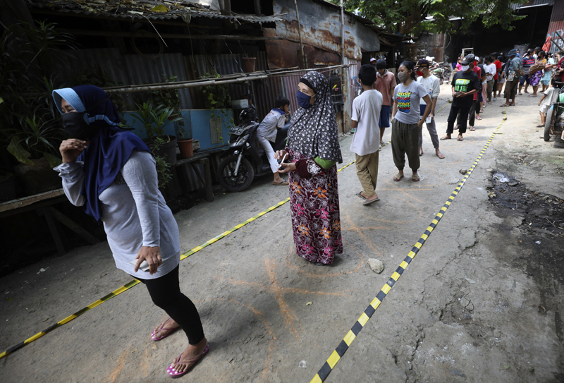 Residents practice social distancing as they queue for donated food during the coronavirus pandemic in a slum area in Jakarta, Indonesia, Wednesday, April 22, 2020. Photo: AP