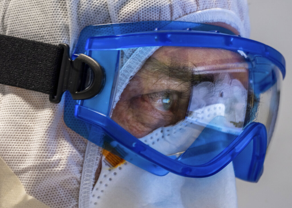 Doctor Giovanni Passeri, wearing protective gear, looks at lungs CT images of his patients inside the COVID-19 section of the Maggiore Hospital in Parma, northern Italy, on Wednesday, April 8, 2020. Passeri says pneumonia caused by the coronavirus shows with a typical ground-glass opacity of the lungs imaging. Photo: AP