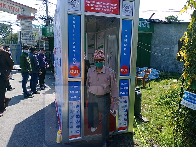 Former health minister and federal lawmaker Khagaraj Adhikari passing through an automated sanitisation tunnel instaled at the premise of Pokhara Health Science Academy, in Pokhara, Tanahun district on Monday, April 20, 2020. Photo: Rishi Baral/ THT