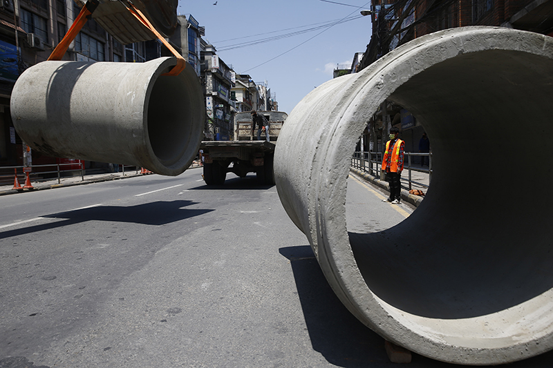 The Department of Roads (DoR) workers carry out construction works to lay sewage pipes on the 28th day of the government imposed lockdown, amid fear of COVID-19 spread, in Kathmandu, on Monday, April 20, 2020. Photo: Skanda Gautam/THT