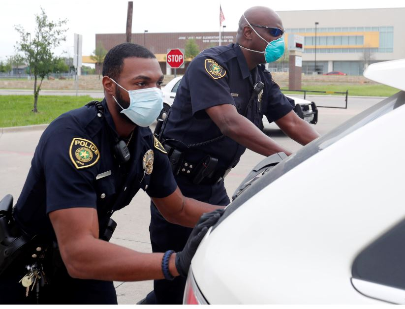 In this April 9, 2020, photo, amid concerns of the spread of COVID-19, Dallas ISD police officers Mylon Taylor, left, and Gary Pierre push a car that ran out of gas while waiting in line for the weekly school meal pick up for students in Dallas. The coronavirus pandemic that has crippled big-box retailers and mom and pop shops worldwide may be making a dent in illicit business, too. Photo: AP