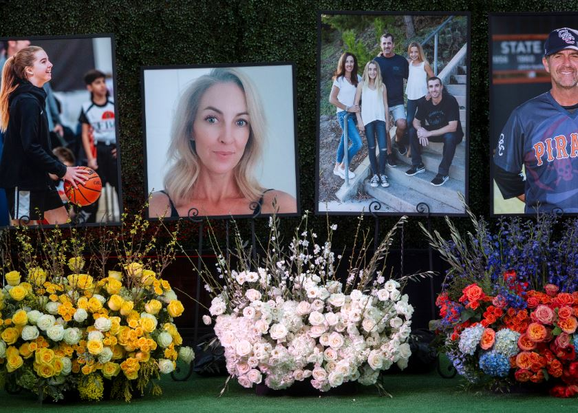 In this Feb. 10, 2020 file photo, flowers and photos honor members of the Altobelli family outside Angel Stadium in Anaheim, Calif. Coach John Altobelli, 56, far right, his wife, Keri, 43, second from left, and his daughter Alyssa, 13, left, died in a helicopter crash on Jan. 26 in Calabasas. Family members of four of the people killed in a helicopter crash with Bryant and his daughter are suing the companies that owned and operated the aircraft. The wrongful death lawsuits were filed electronically Sunday, April 19, 2020 in Los Angeles Superior Court on behalf of three members of one family and a woman who helped coach Bryant's daughter in basketball. One suit was filed by two children of Orange Coast College baseball coach John Altobelli,his wife and daughter, who played basketball with Gianna. Another suit was filed by the husband and three children of Christina Mauser, who helped Bryant coach the girls' basketball team. File Photo: AP