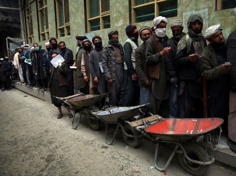 Daily-wage workers wait in line to receive free wheat donated by Afghan businessmen ahead of the upcoming holy fasting month of Ramadan in Kabul, Afghanistan, Monday, April 20, 2020. Muslims across the world are observing the holy fasting month of Ramadan, when they refrain from eating, drinking and smoking from dawn to dusk. Photo: AP