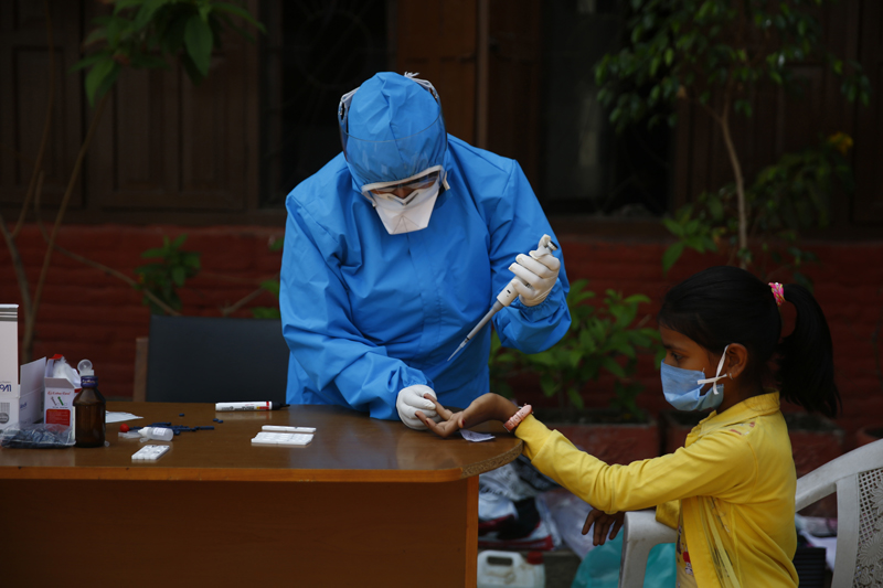 FILE - A health worker performs a rapid test on a girl who travelled from abroad, at Basantapur Durbar Square, in Kathmandu, on the 26th day of lockdown, on Saturday, April 18, 2020. Photo: Skanda Gautam/THT