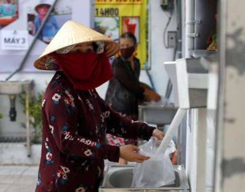 A woman fills a plastic bag with rice from a 24/7 automatic rice dispensing machine 'Rice ATM' during the outbreak of the coronavirus disease (COVID-19), in Ho Chi Minh, Vietnam, April 11, 2020. Photo: Reuters