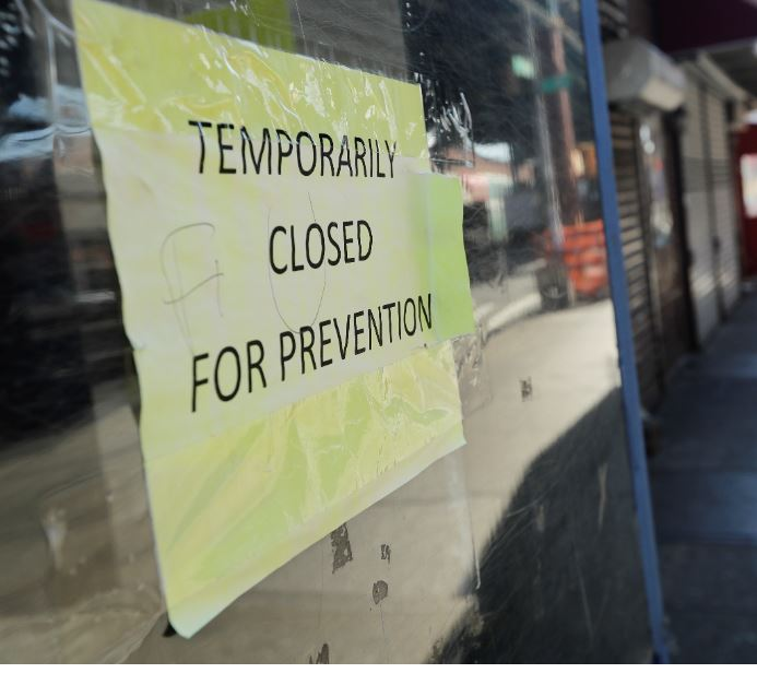In this April 4, 2020, file photo, pedestrians pass closed stores on Roosevelt Avenue in the Queens borough of New York. The coronavirus crisis is upending service businesses, and the crisis may permanently change the way Americans work, shop and socialize, even after the disease fades away. File Photo: AP
