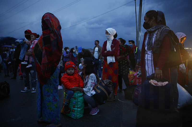 People waiting to board a bus to return to their villages on the 29th day of the government-imposed lockdown amid concerns about the spread of  coronavirus pandemic, in Kathmandu, on Tuesday,  April 21, 2020. Photo: Skanda Gautam/ THT