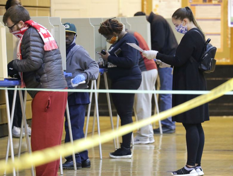 An election official cleans a voting booth before a person votes at Riverside High School, in Milwaukee on Tuesday, April 7, 2020. The Wisconsin primary is moving forward in the wake of the coronavirus epidemic after Gov. Tony Evers sought to shut down Tuesday's election in a historic move Monday that was swiftly rejected by the conservative majority of the Wisconsin Supreme Court by the end of the day. Photo: AP