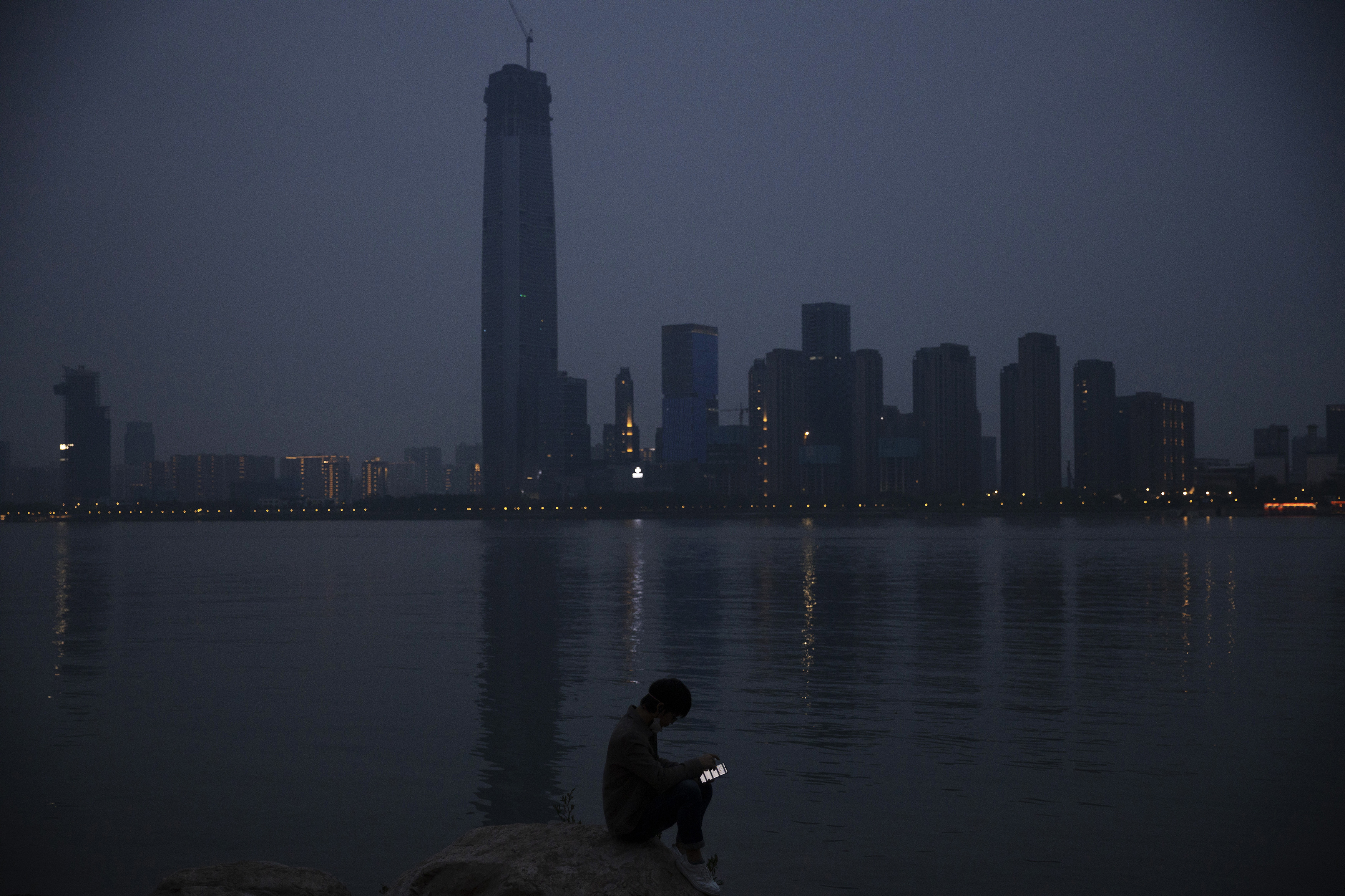 A man checks his mobile phone along the Yangtze River in Wuhan in central China's Hubei province. As governments around the world consider how to monitor new coronavirus outbreaks while reopening their societies, many are starting to bet on smartphone apps to help stanch the pandemic. File Photo: AP