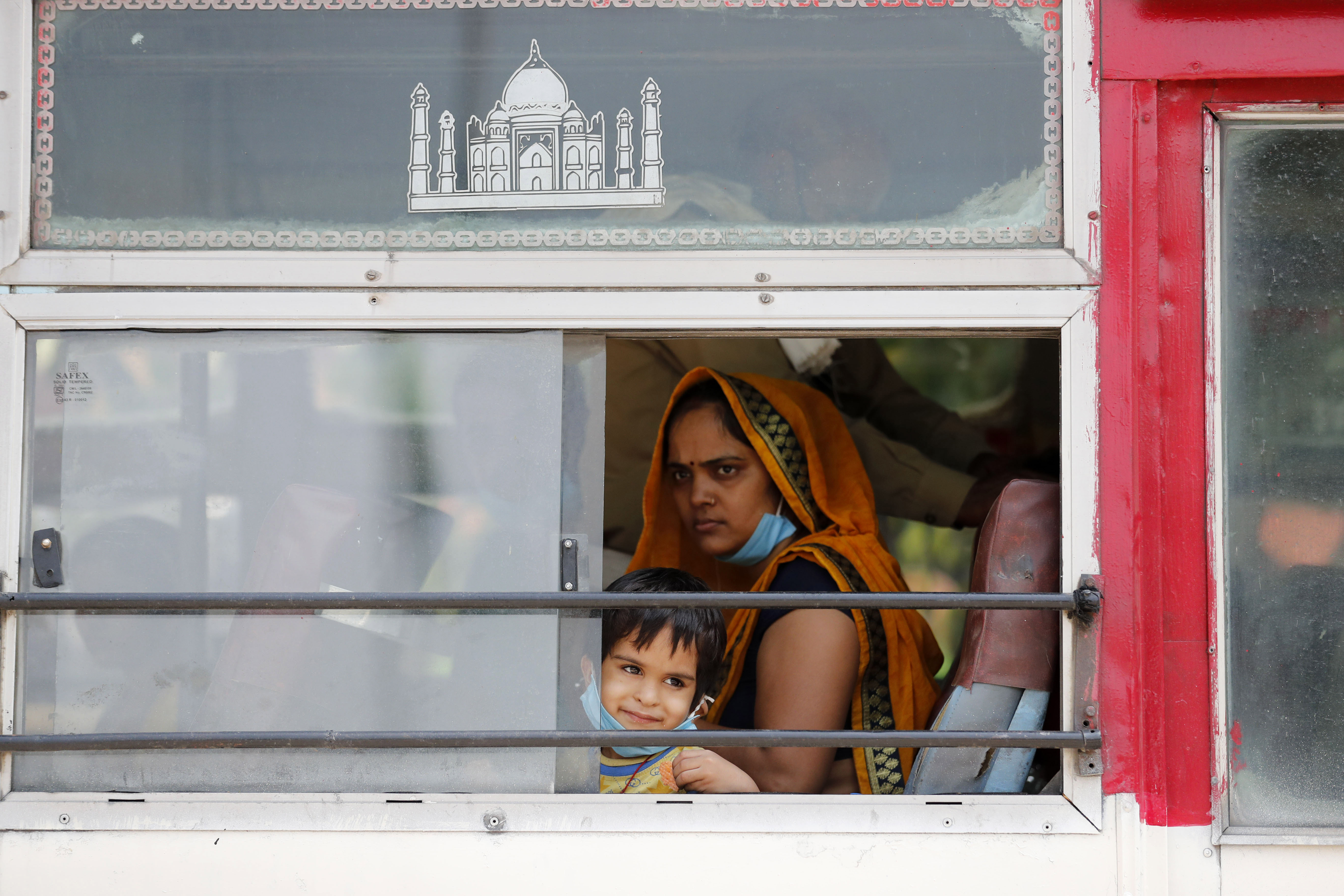 A migrant laborers, who arrived from Gujarat state on a train, sits with a child inside a bus as they prepare to leave for their native villages in their home state of Uttar Pradesh in Prayagraj, India, Wednesday, May 6, 2020. India is running train service for thousands of migrant workers desperate to return home since it imposed a nationwide lockdown to control the spread of the coronavirus. Photo: AP