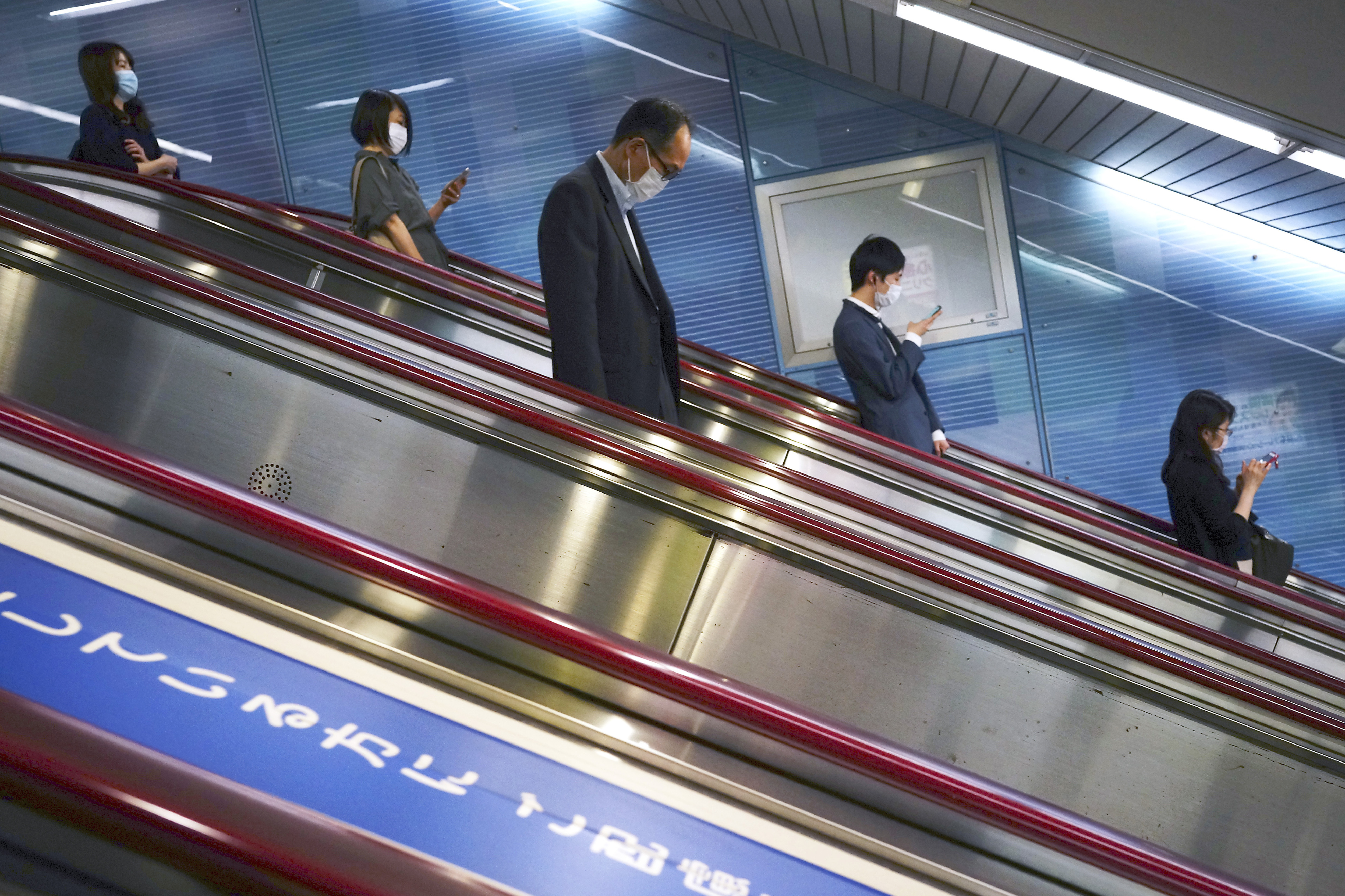 People wearing face masks to help curb the spread of the coronavirus ride an escalator into a subway station in Tokyo Monday, May 11, 2020. Japan has extended a state of emergency until the end of May. Photo: AP