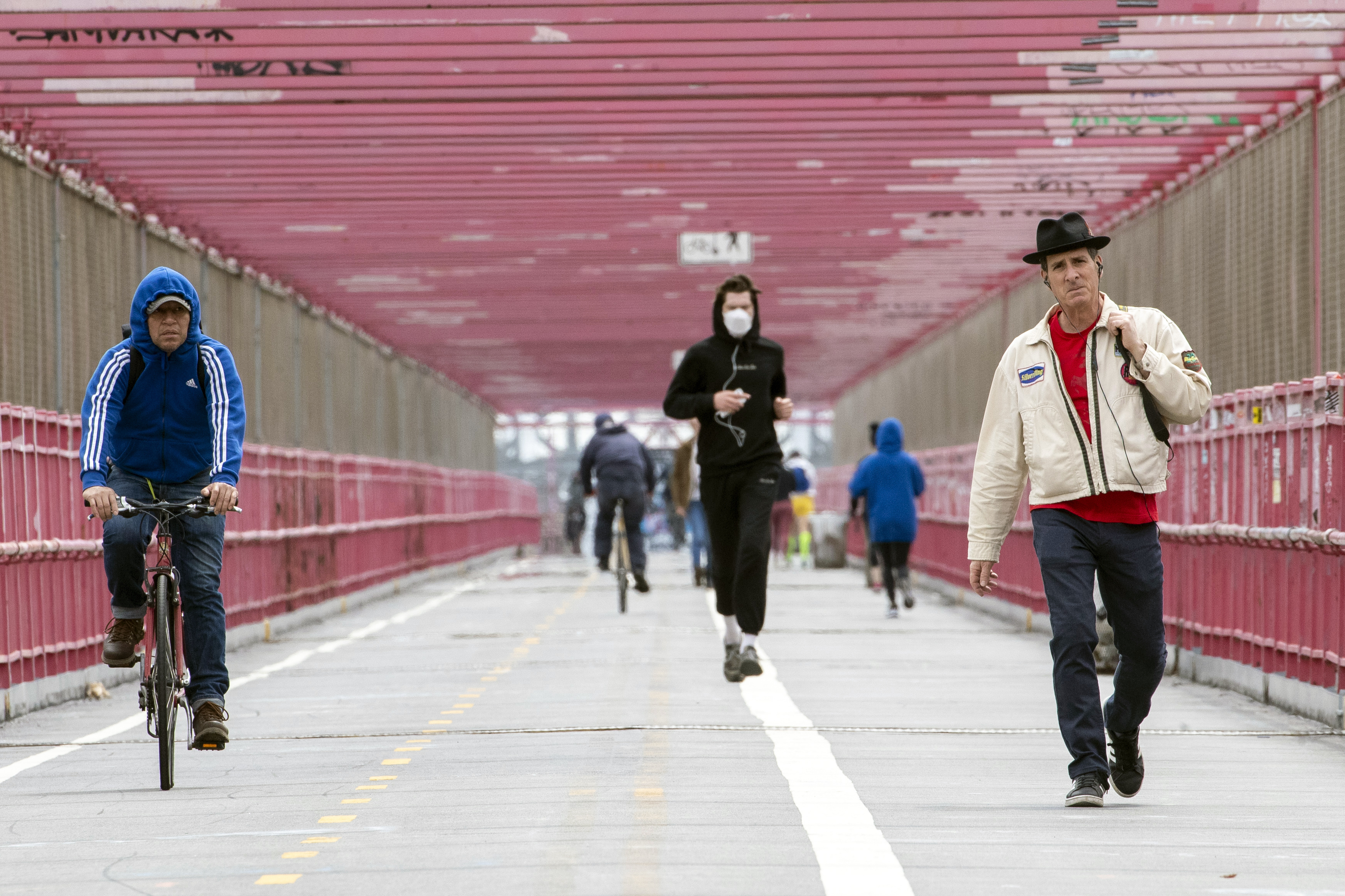 In this Monday, May 11, 2020 photo, a jogger wearing a face masks runs in between a biker and a pedestrian not wearing masks as they make their way over the Williamsburg bridge in New York.New York's governor has ordered masks for anyone out in public who can't stay at least six feet away from other people. Yet, while the rule is clear, New Yorkers have adopted their own interpretation of exactly when masks are required, especially outdoors. Photo: AP